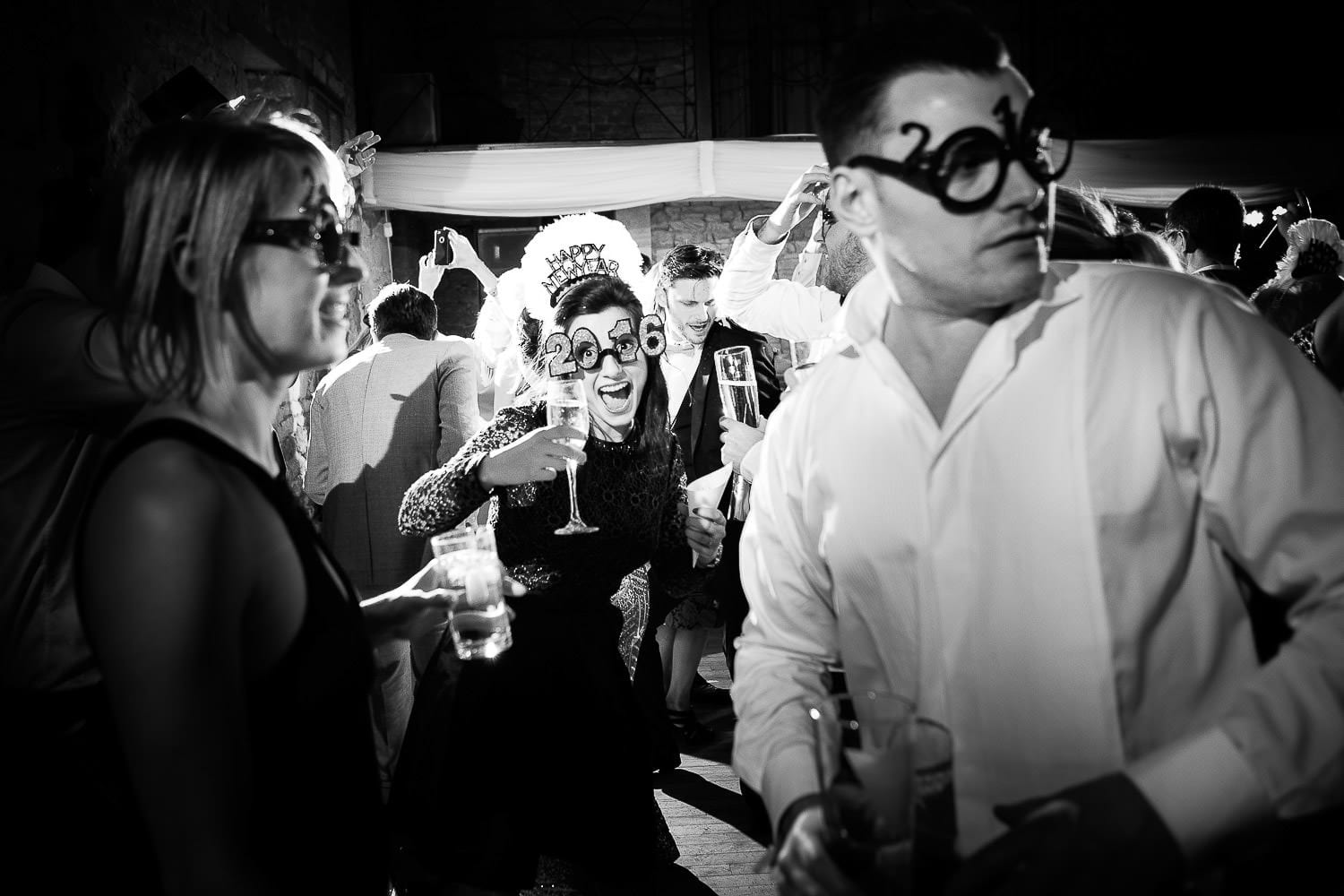Black and white image of guests wearing new years eve props