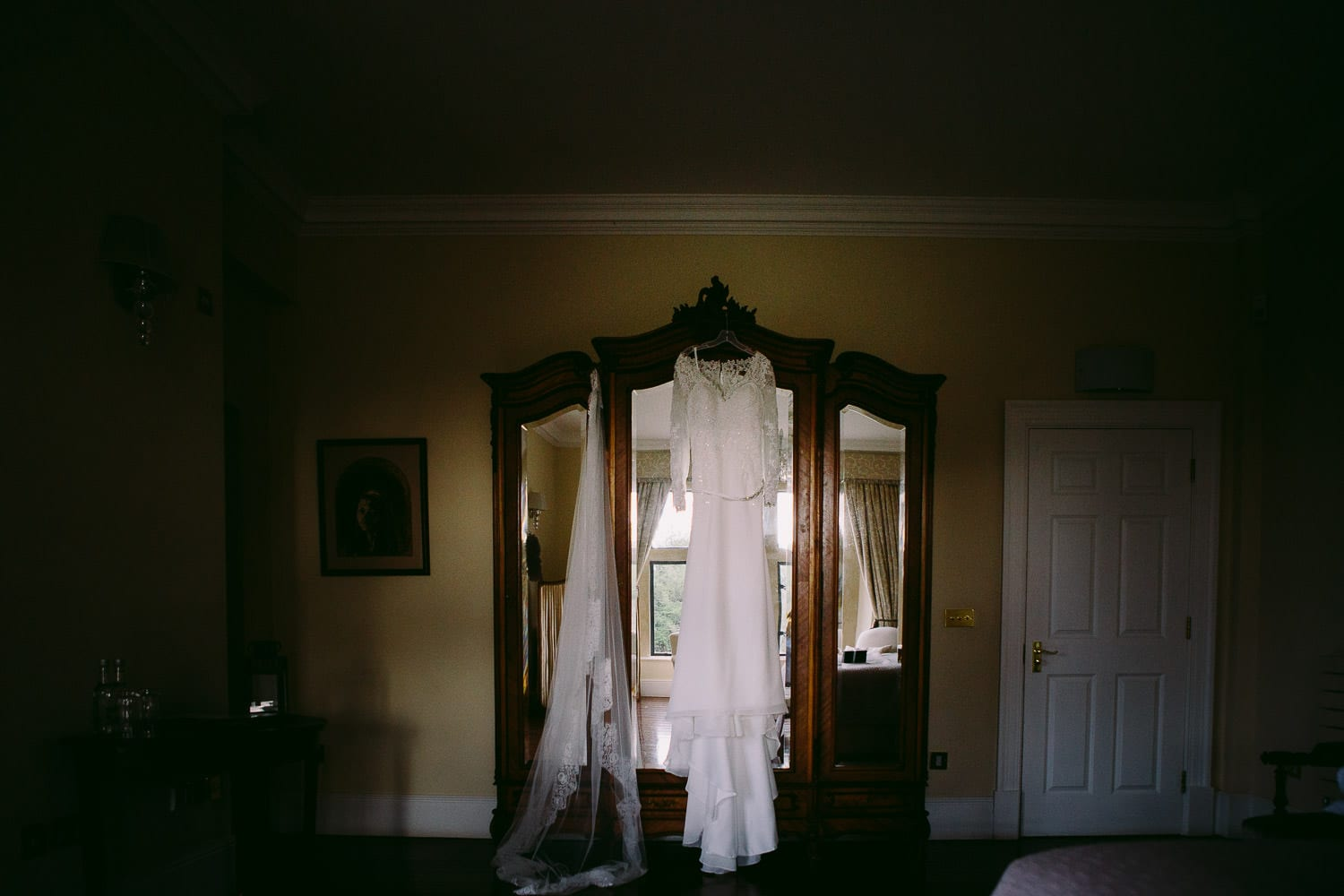 A wedding dress hanging on a wardrobe in the bridal suite