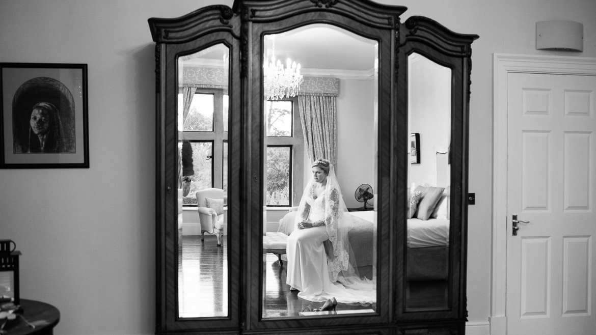 A black and white image of a bride sat on her own, reflected in a mirror