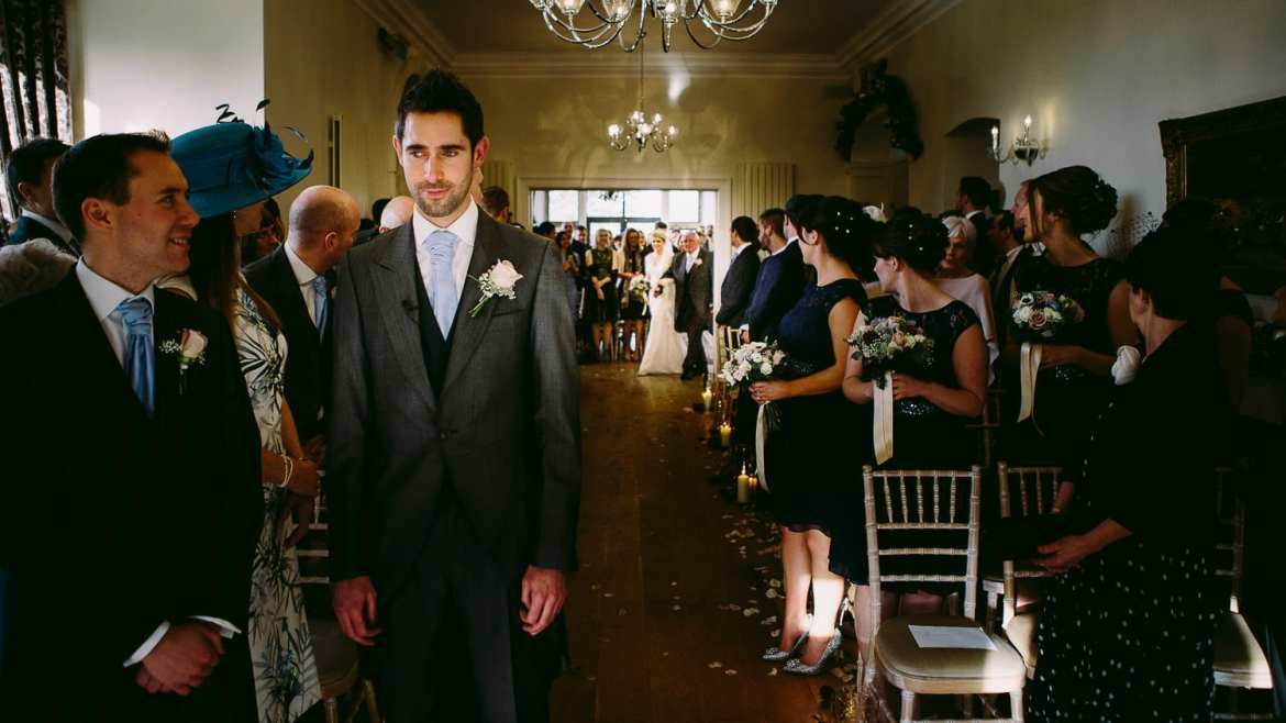 The groom waits at the altar while the bride arrives in the background
