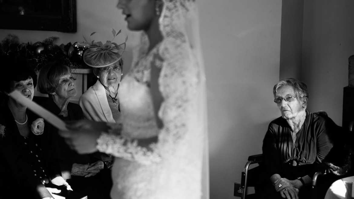 Grandparents look on as the bride gives a reading during her marriage ceremony