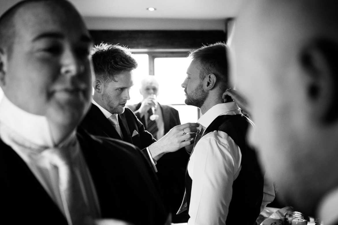 The brother of the groom helps with his tie