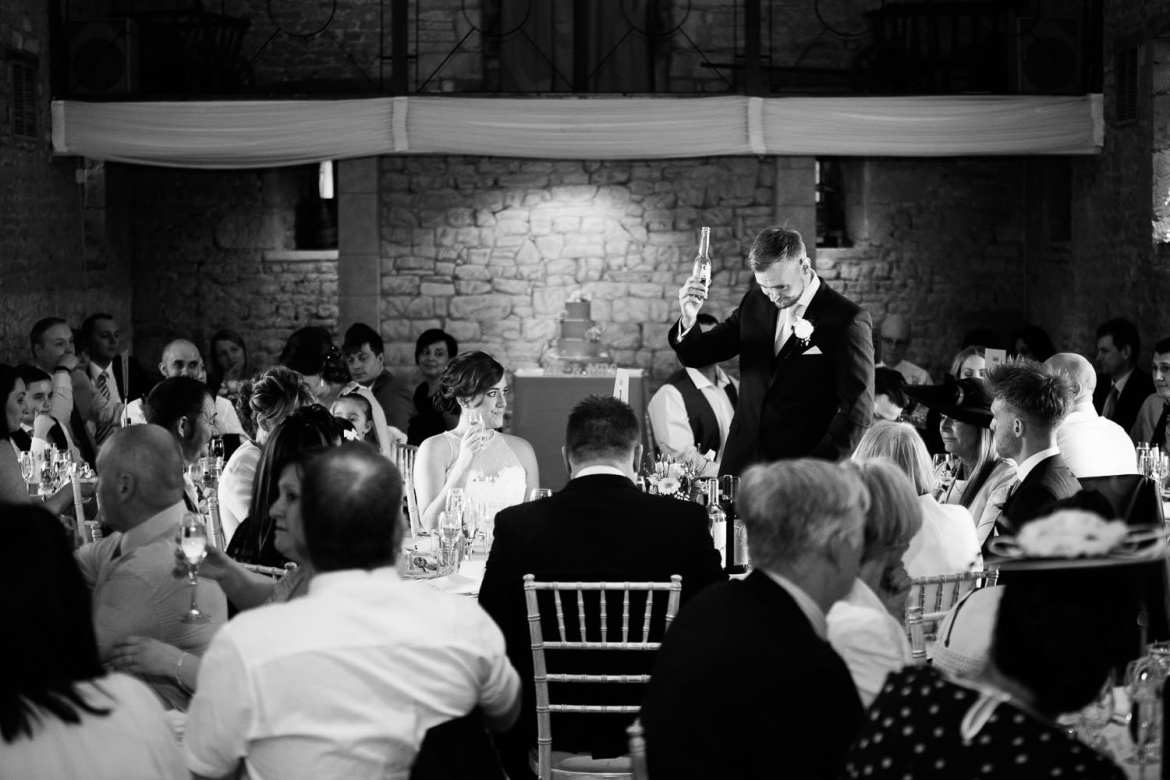 The groom stands and toasts the bride