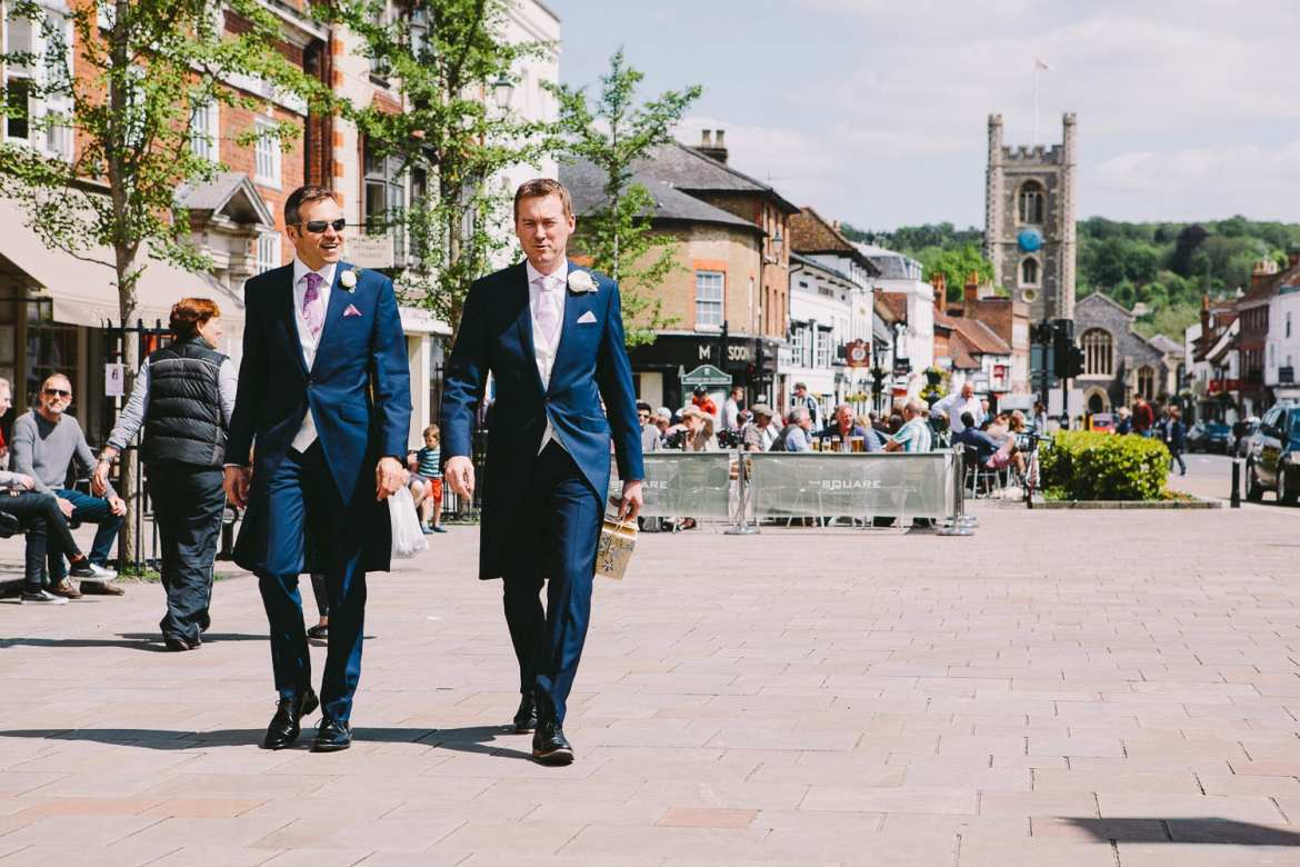 The groom and best man walking through Henley town centre to the Town Hall