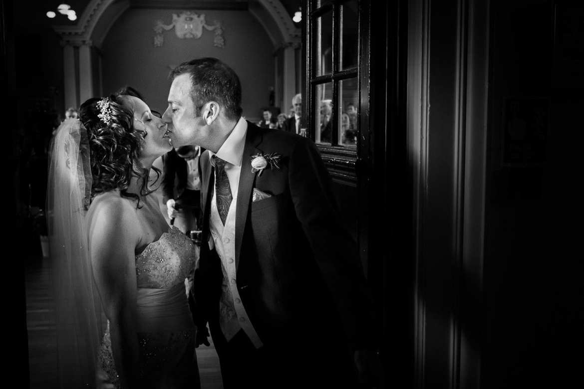 Bride and groom share a kiss outside the ceremony room at Henley Town Hall