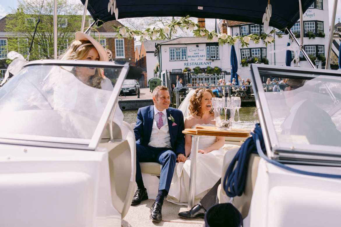 Bride and groom ride back along the Thames to Greenlands wedding venue