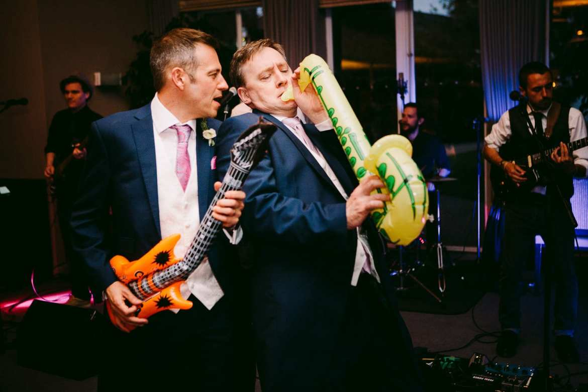 Groom and groomsmen dancing with blow up musical instruments at Greenlands