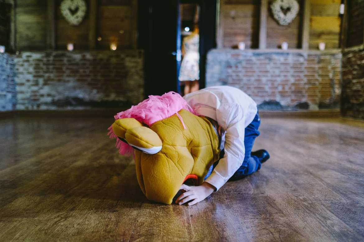A child on the floor wearing a muppet head