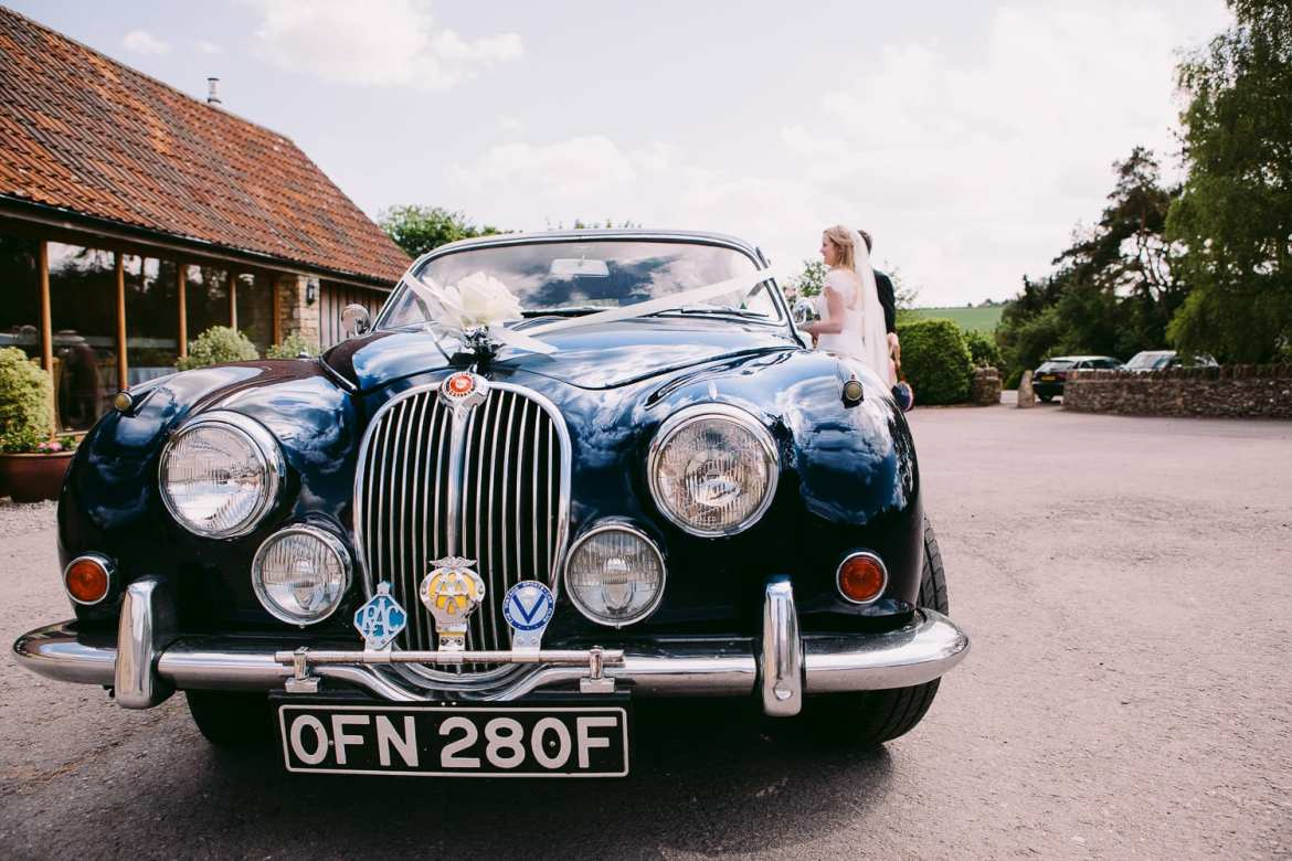 The wedding car arrives at Kingscote Barn