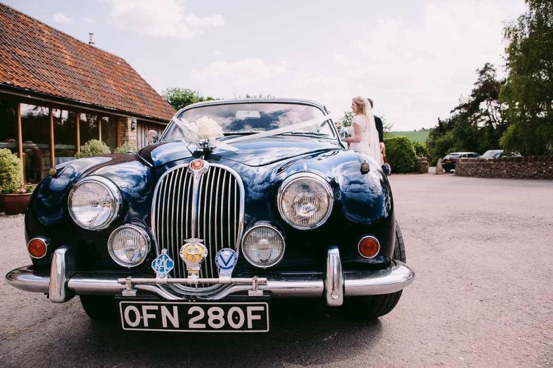 The wedding car arrives at Kingscote Barn