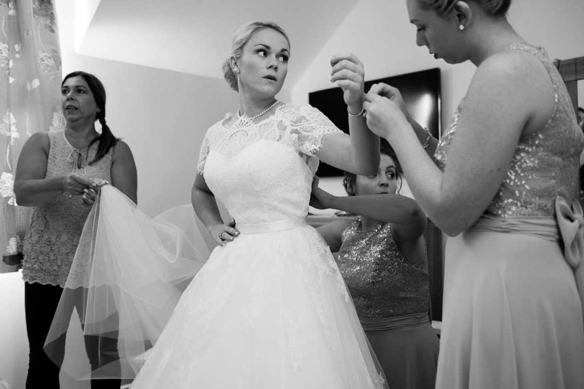 The bride in her dress having her jewellery put on