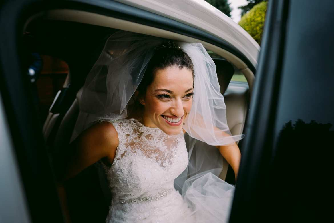 A smiling bride arrives at the church