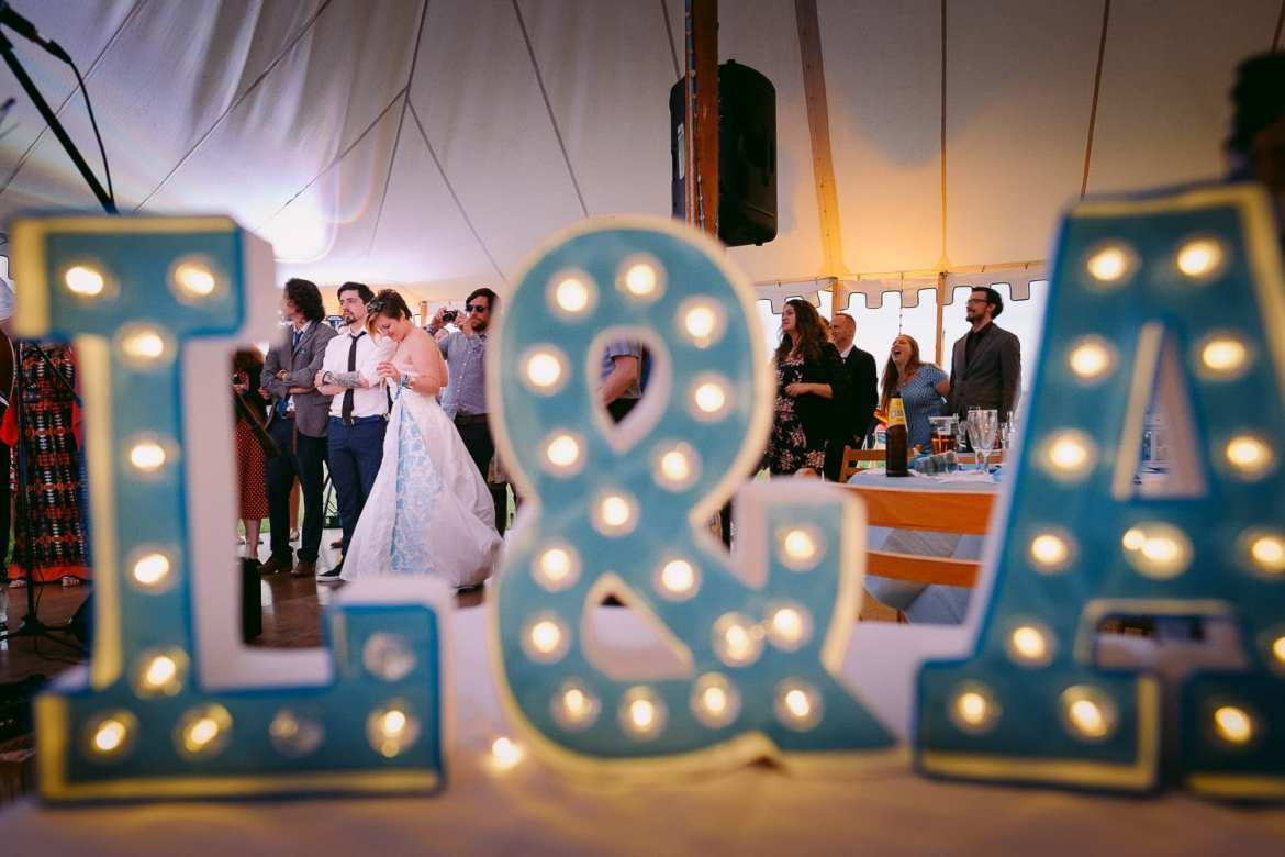 The bride and groom behind lights with their initials