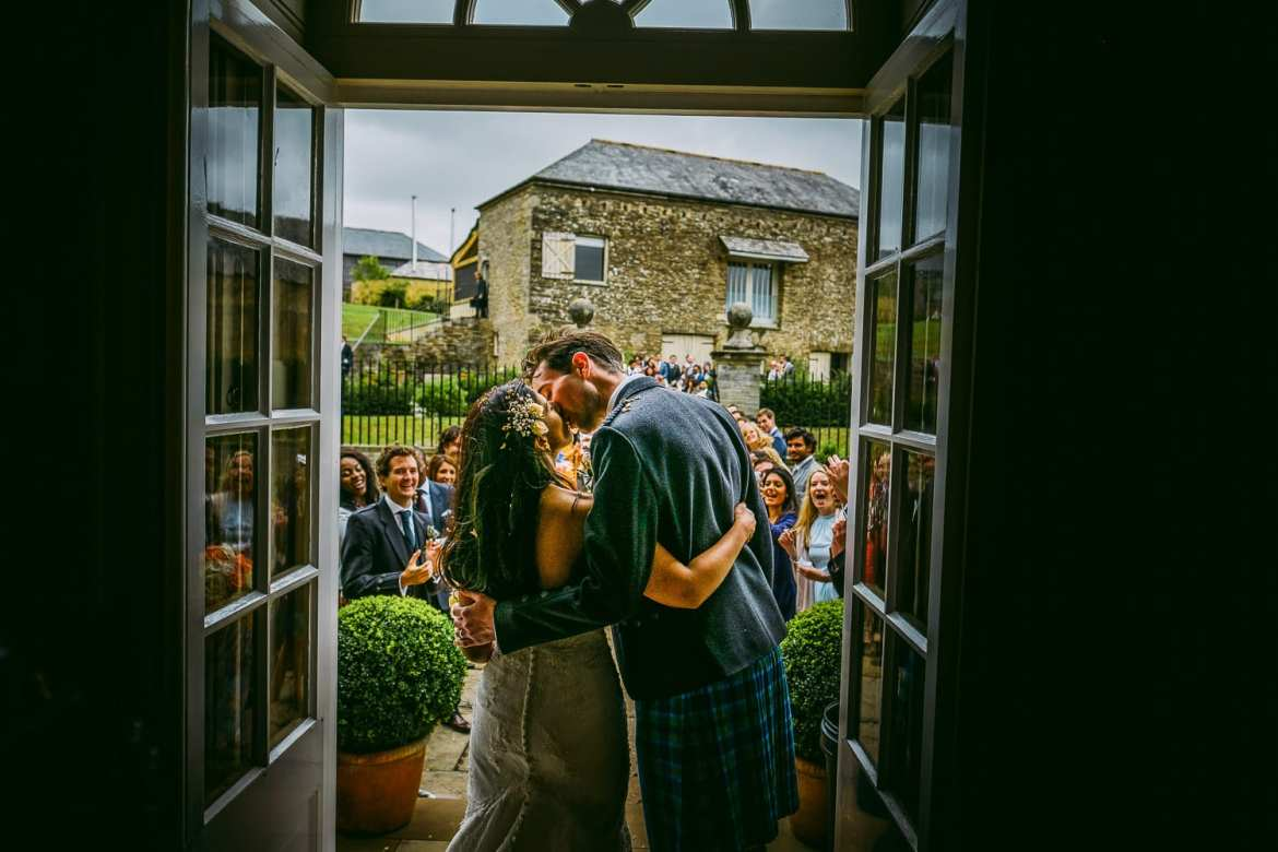 The newlyweds kiss on the steps of Shilstone House