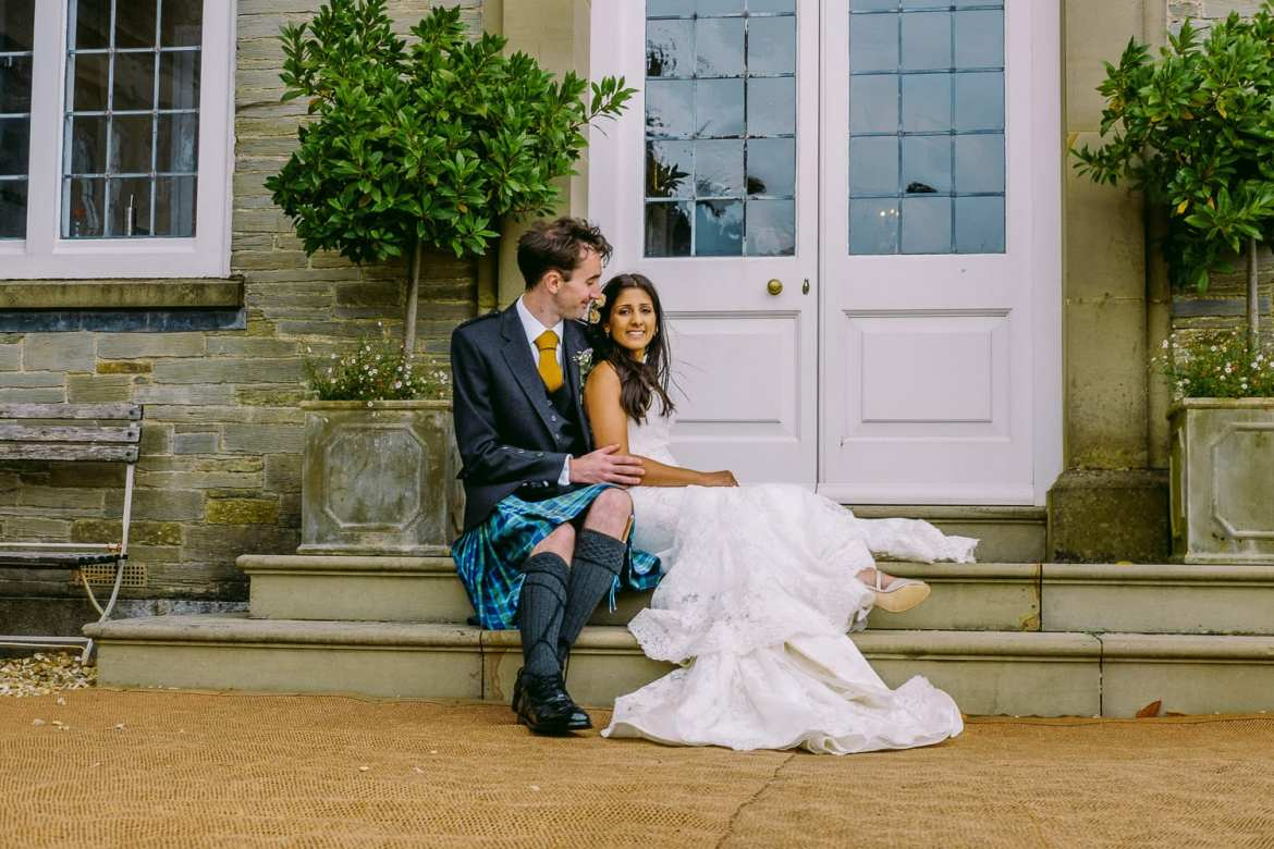 The bride and groom sitting on the steps at the rear of Shilstone House