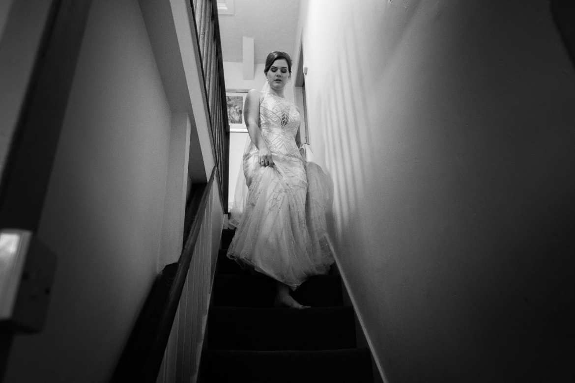 The bride comes down the stairs in her dress