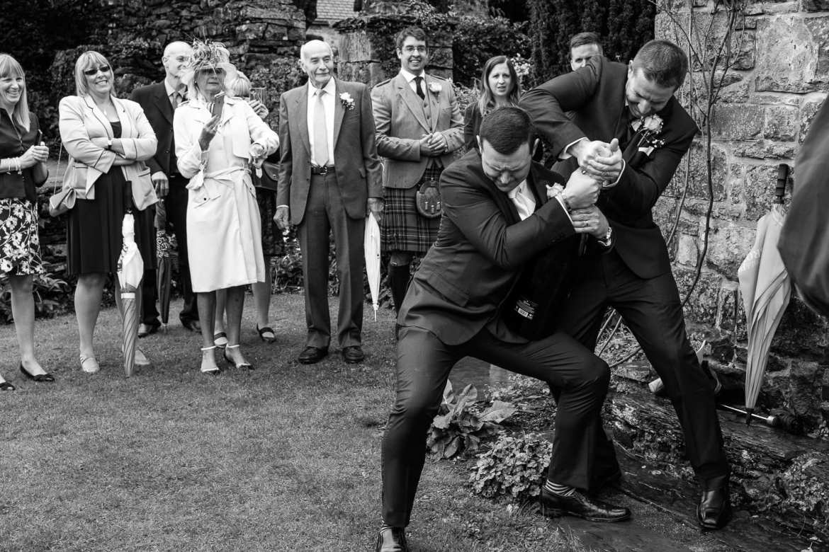 The groom and best man still fight to open the champagne