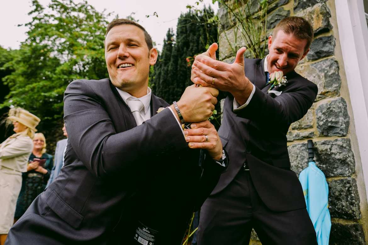 The groom and best man fight to open the champagne. It took a while