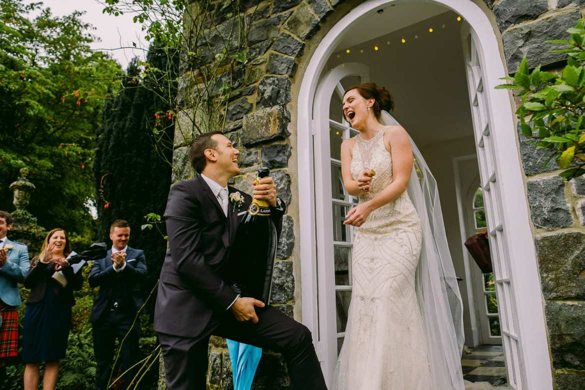 The bride and groom laugh as the champagne pops