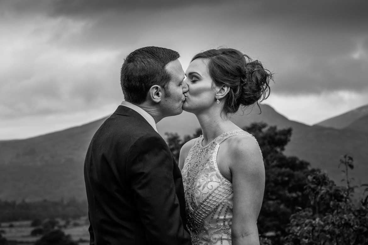 The bride and groom kiss with the mountains in the background