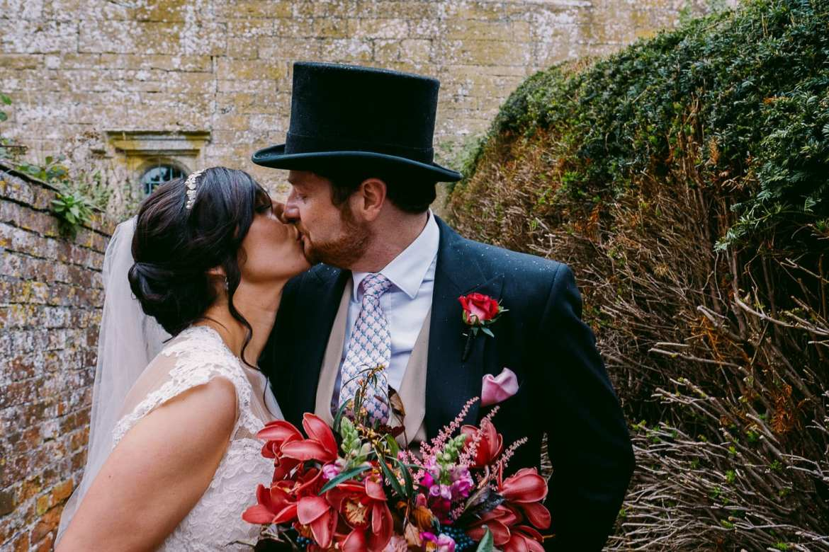 The newlyweds kiss outside Brympton House