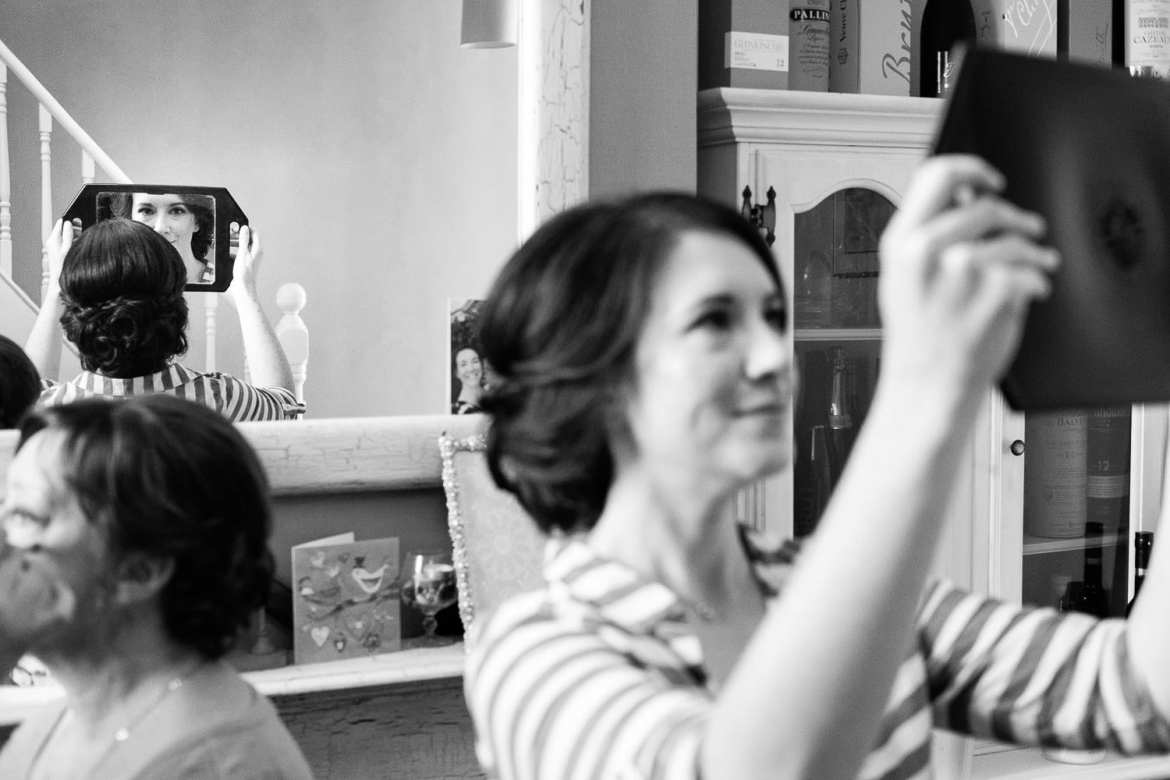 The bride checks her hair out in the mirror