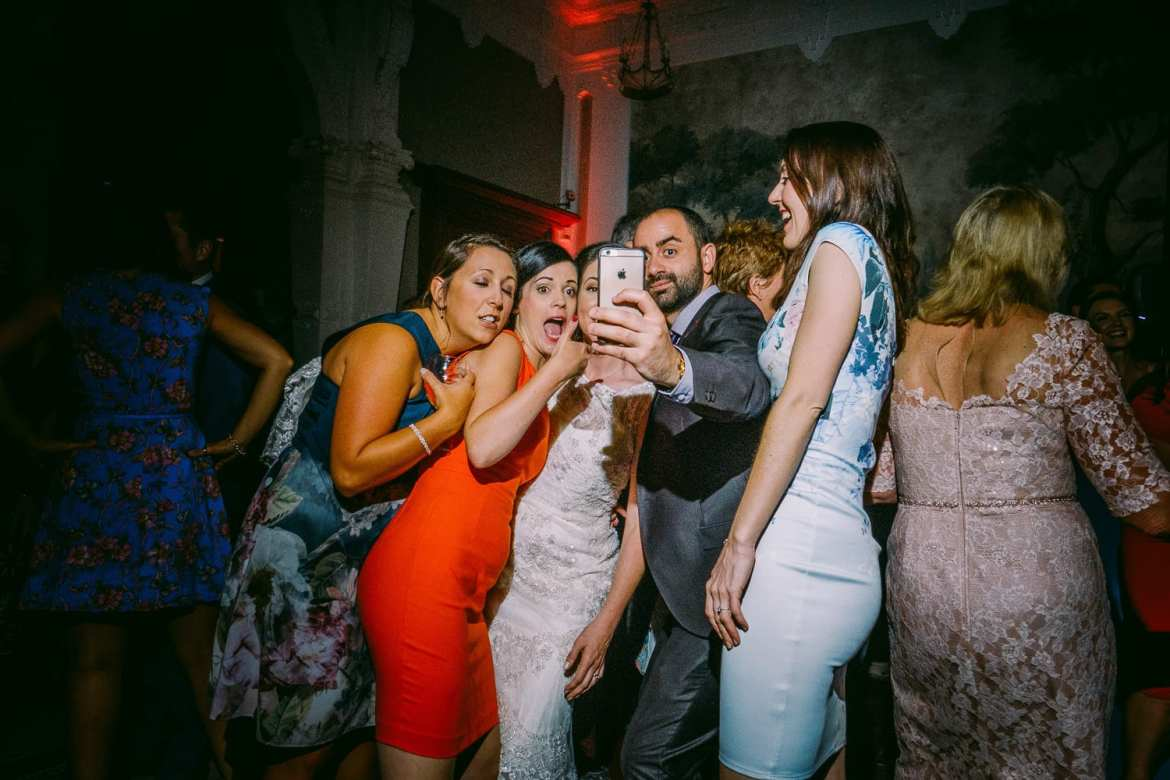 Wedding guests taking a selfie with the bride