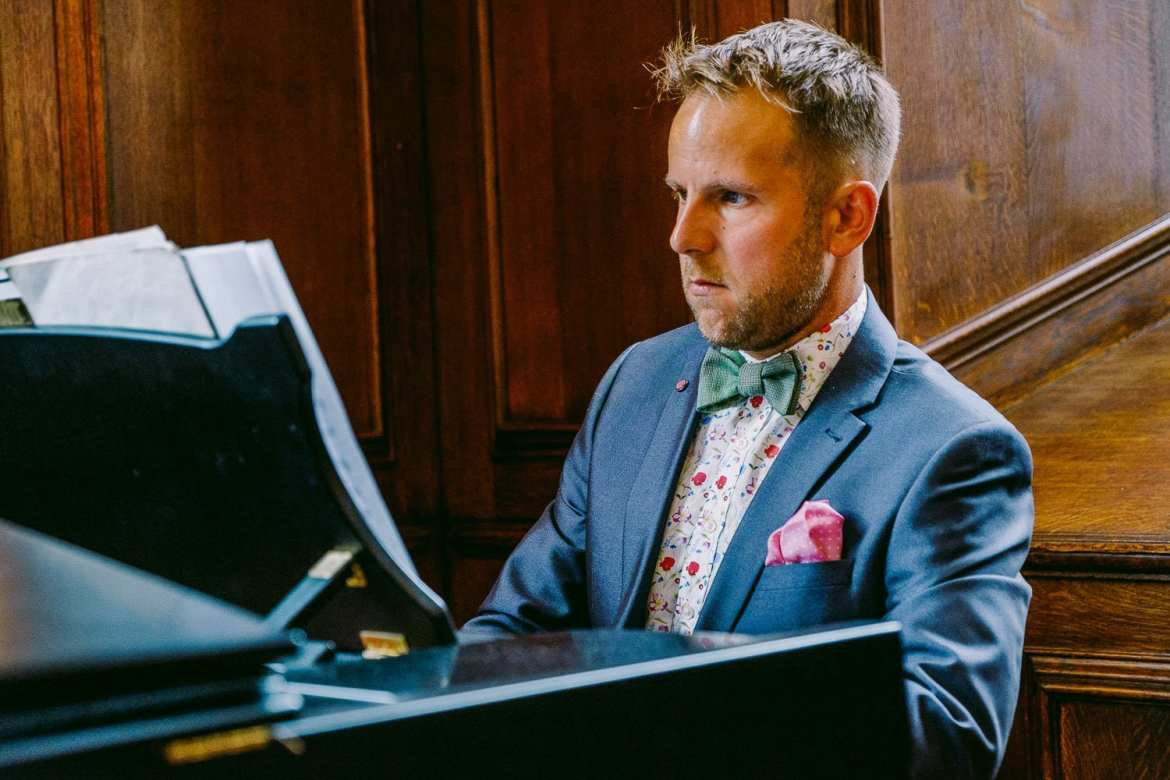 A guest plays the piano at a same sex wedding in Cambridge