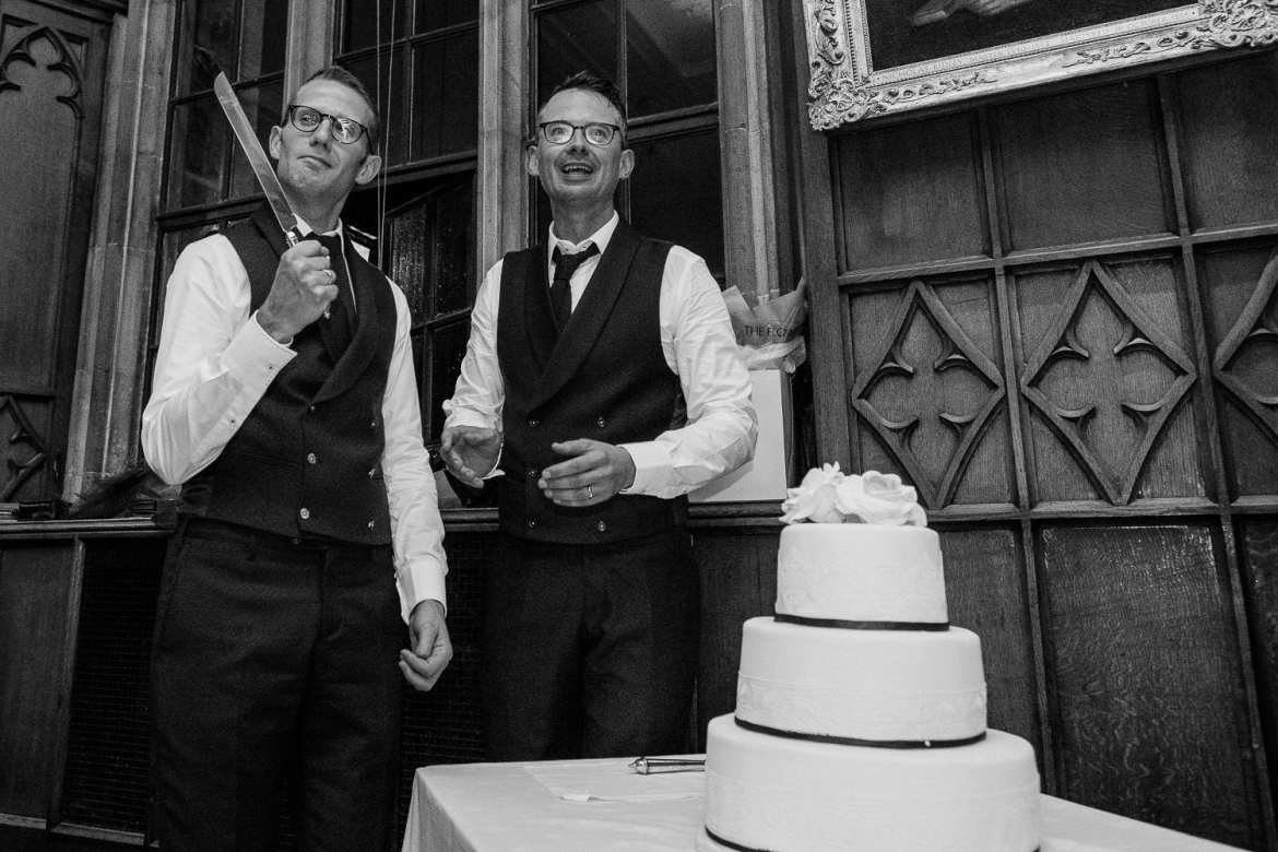 A groom wields the knife during the cake cutting