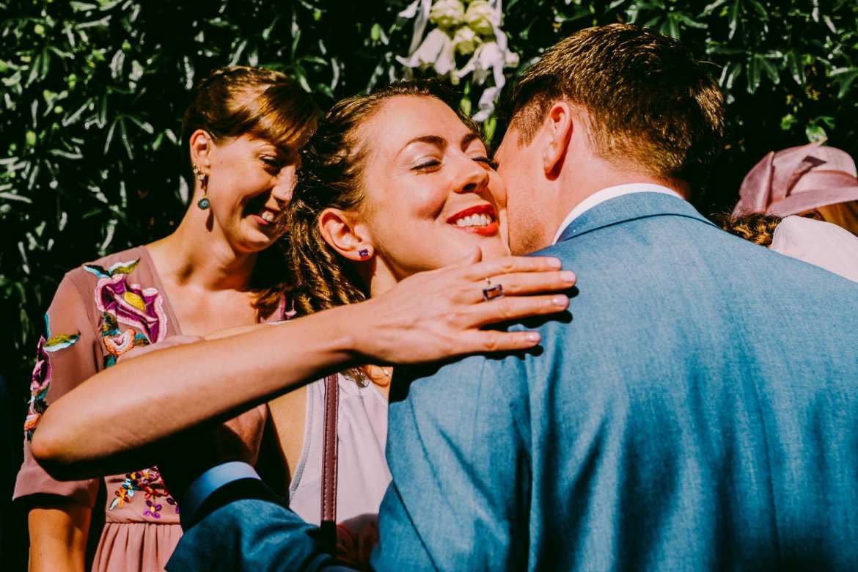 A wedding guest congratulates the groom