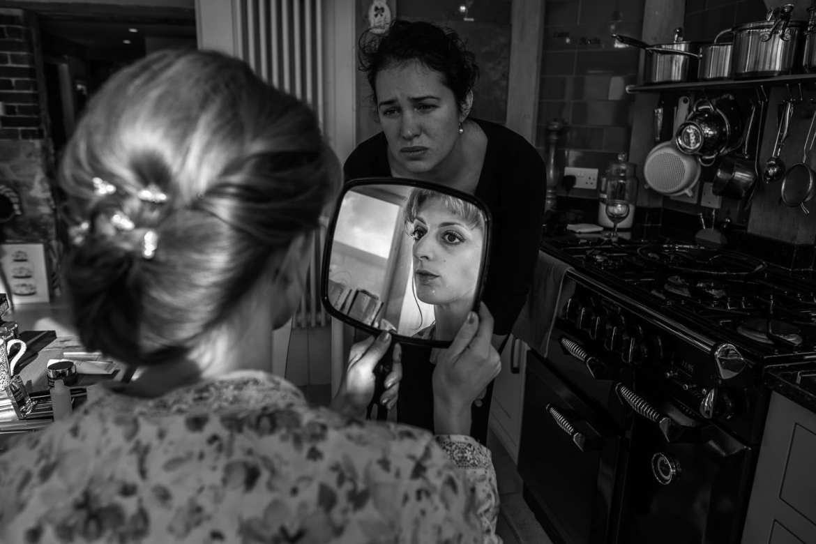Black and white image of bride's reflection in mirror