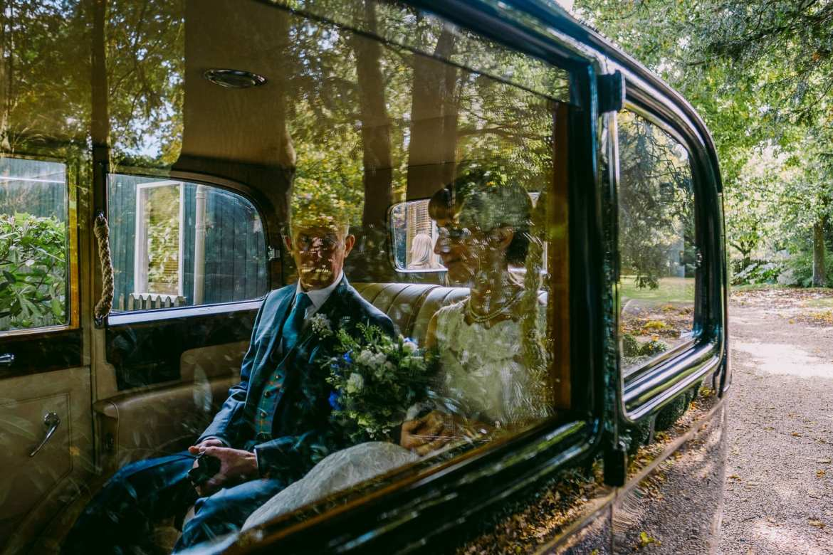 Bride and her father through the car window
