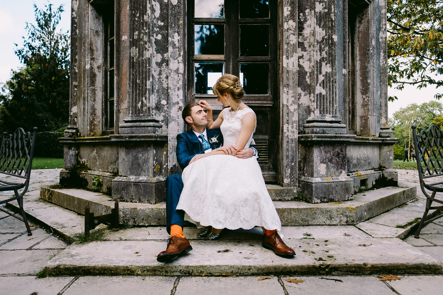 Bride and groom sitting on steps in the garden