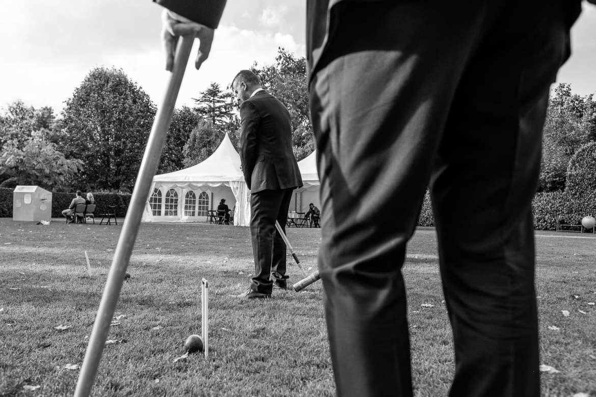 Black and white shot of guests playing croquet