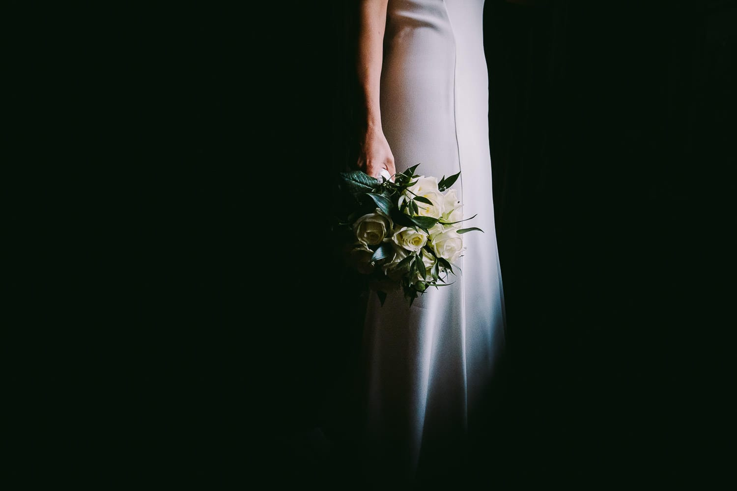 Bride holding her bouquet stood in front of window with background in darkness