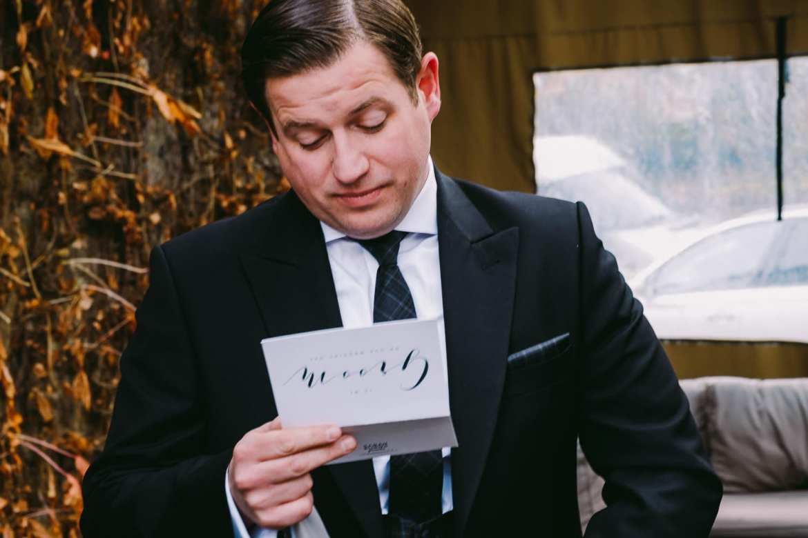 The groom reads a card from his bride