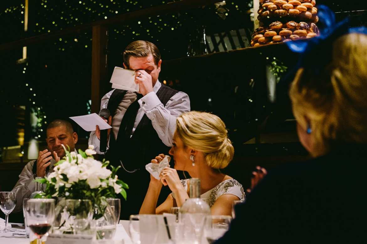 The groom wipes a tear from his eye during the speech