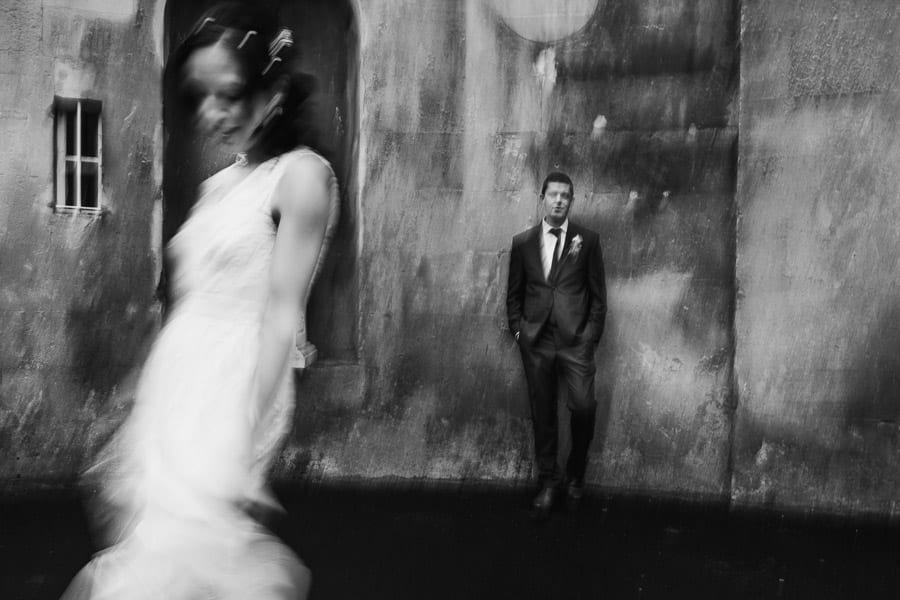 A portrait of a bride dancing in front of her groom. Shot at a slow shutter speed outside Bailbrook House in Bath