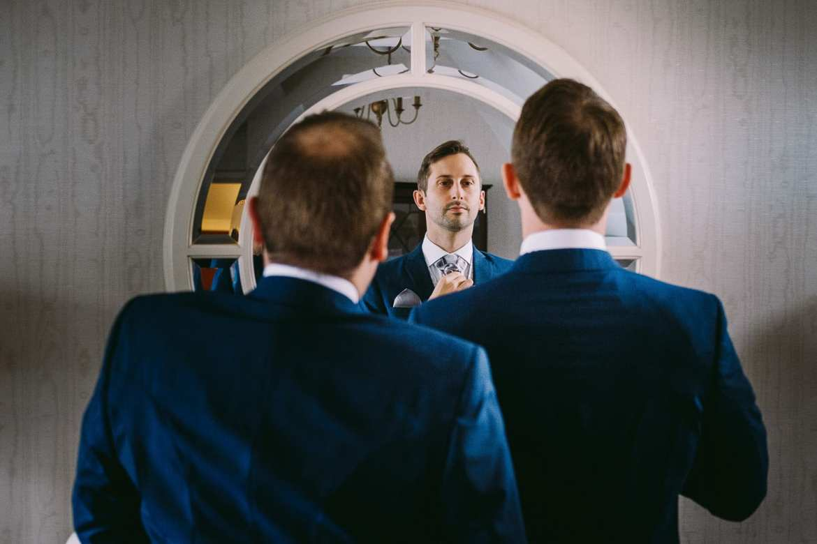 Reflection of groom and best man in the mirror