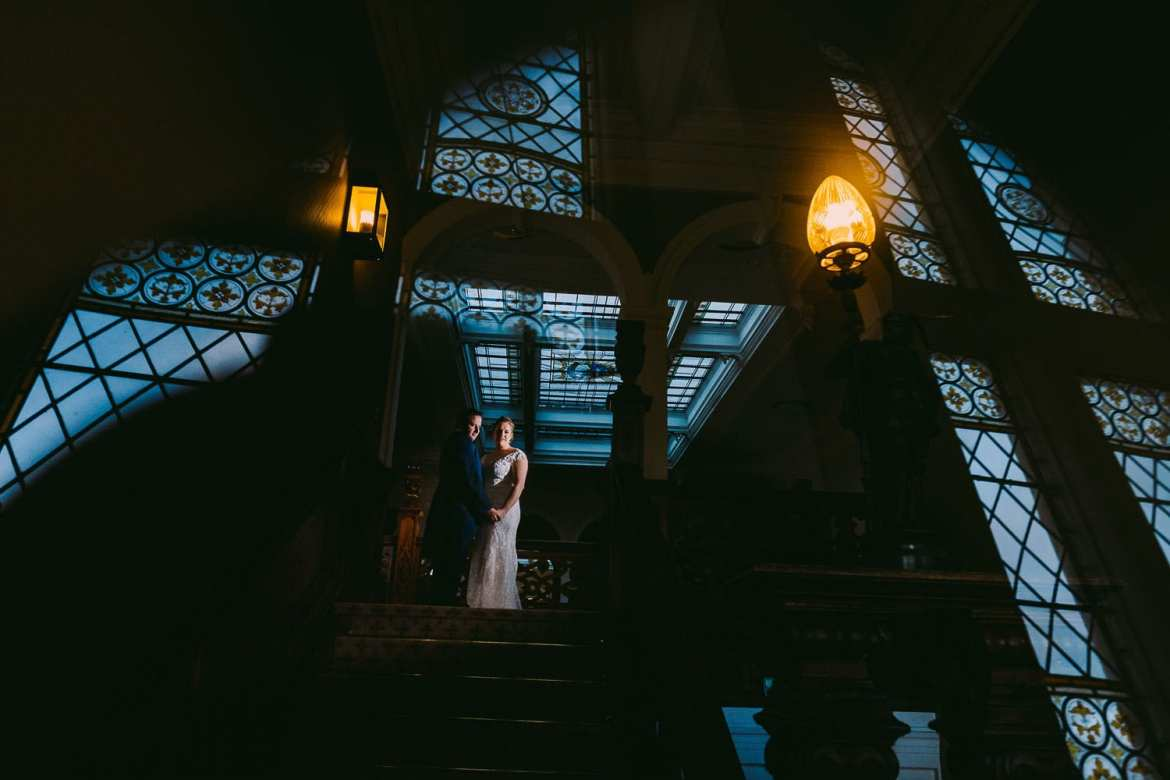 Bride and groom on the staircase by stained glass window