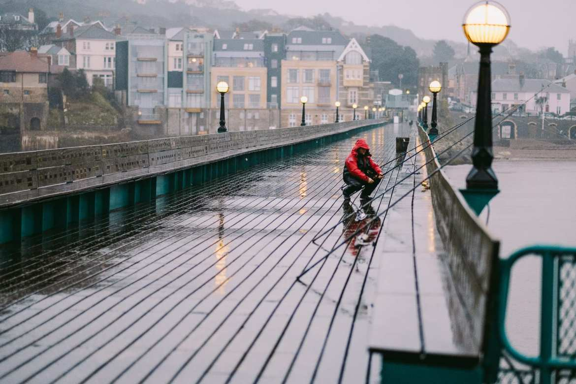 A fisherman on clevedon pier in the rain