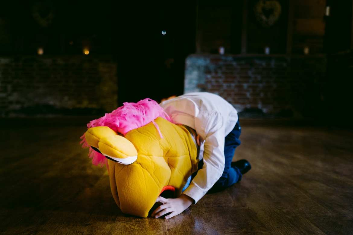 A child lays on the floor wearing a big muppet head