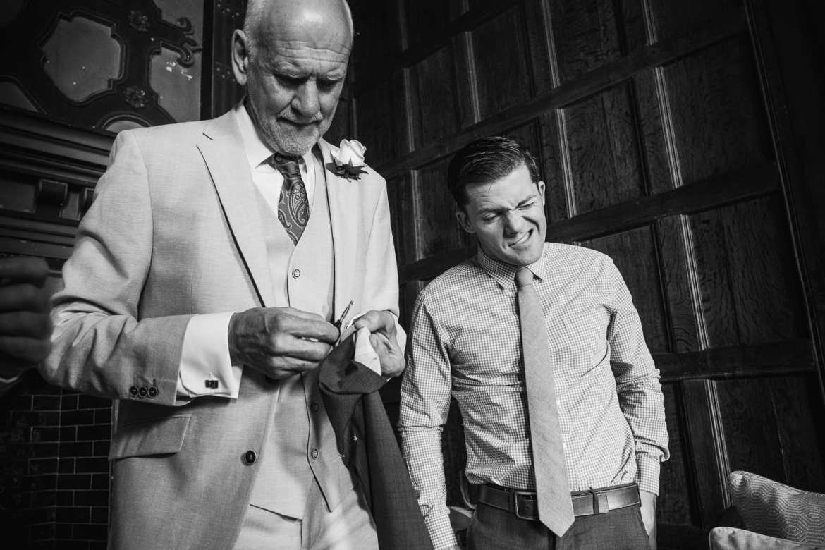 The groom's father cuts a label off a suit