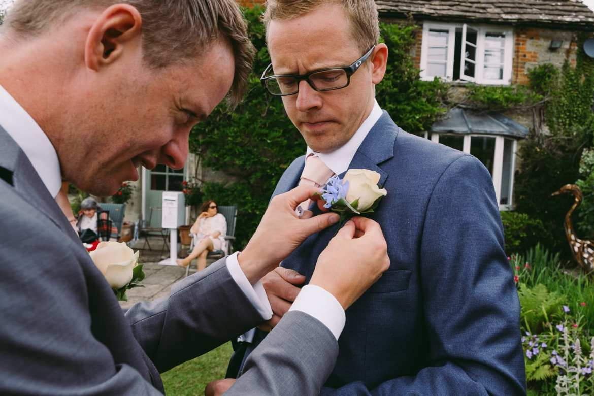 The best man fixes the groom's corsage
