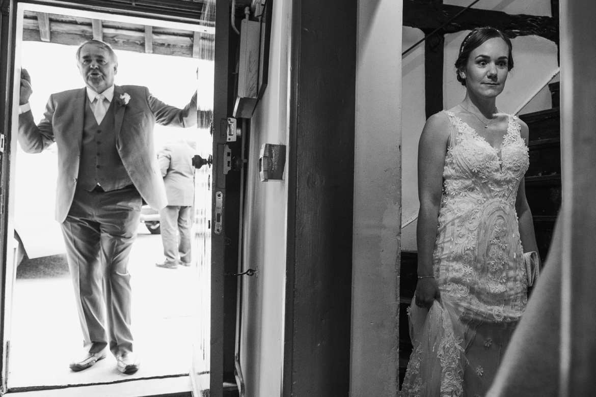 The father of the bride waits at the door for his daughter