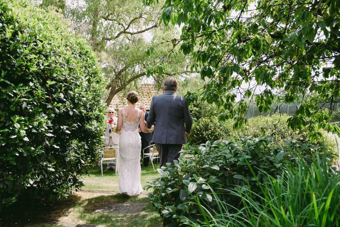 The bride and father of the bride walk through the garden towards the wedding ceremony