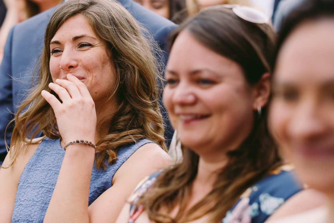 Wedding guests smiling while watching the wedding