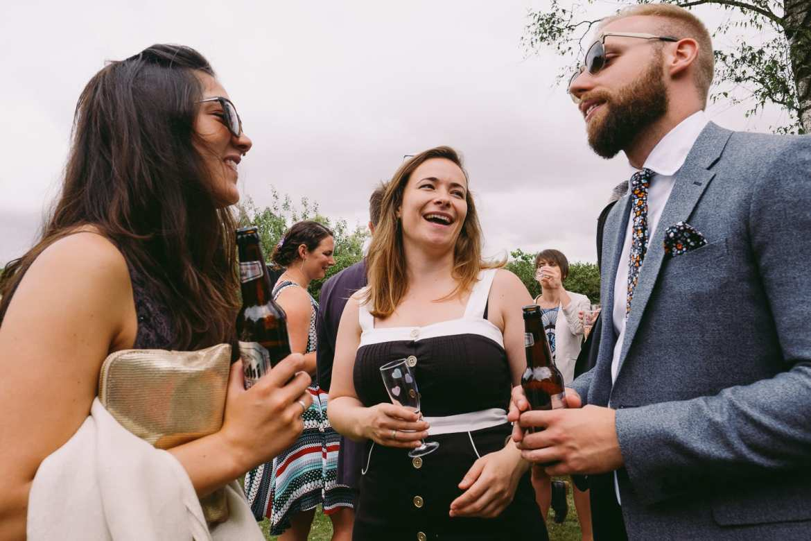 Young wedding guests laughing and talking