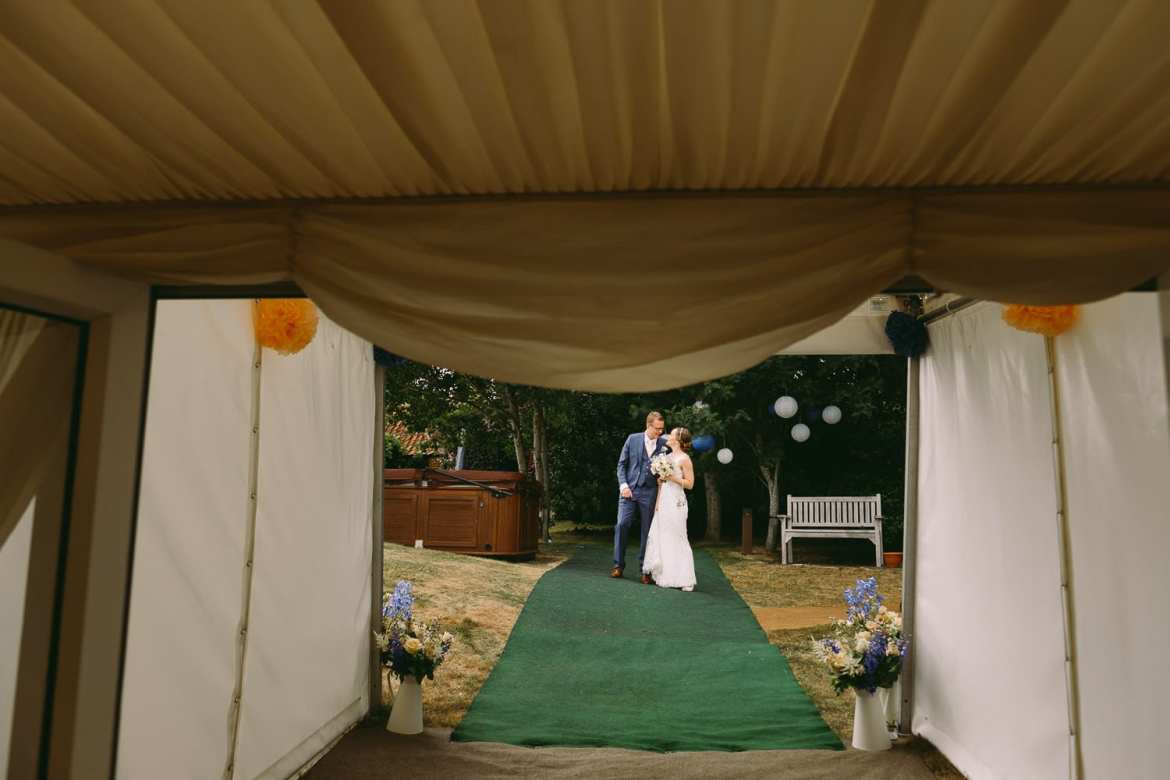 The bride and groom wait to be announced into the garden marquee