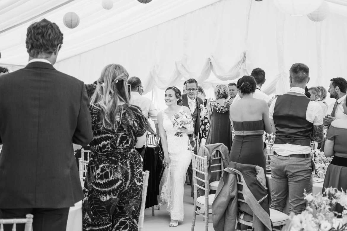 The newlyweds enter the wedding breakfast while the guests cheer them